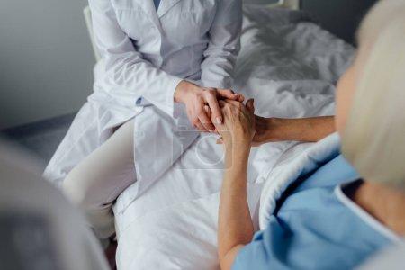 Photo pour Vue partielle du médecin féminin tenant la main avec une femme âgée couchée au lit à l'hôpital - image libre de droit