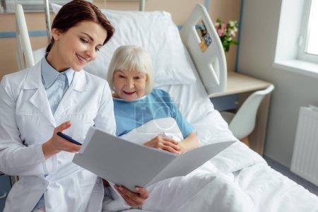 Photo pour Beau sourire femme médecin holding diagnostic et Conseil haute femme couché dans son lit d'hôpital - image libre de droit