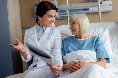 Photo pour Sourire de femme médecin tenant diagnostic et Conseil haute femme couché dans son lit d'hôpital - image libre de droit