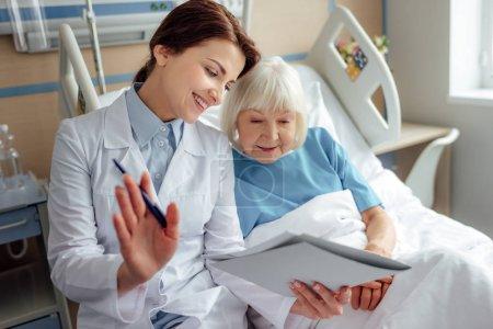 Photo pour Heureuse femme médecin tenant diagnostic et Conseil haute femme couché dans son lit d'hôpital - image libre de droit