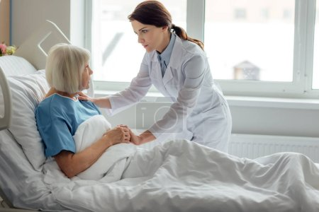 female doctor holding hands and supporting sad senior woman lying in hospital bed