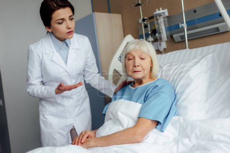 female doctor holding hands and consulting upset senior woman lying in hospital bed