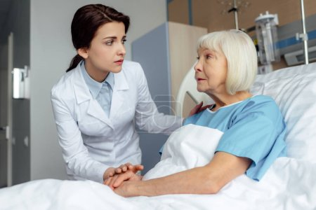 worried female doctor holding hands and consulting senior woman lying in hospital bed