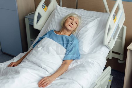 sad lonely senior woman lying in hospital bed
