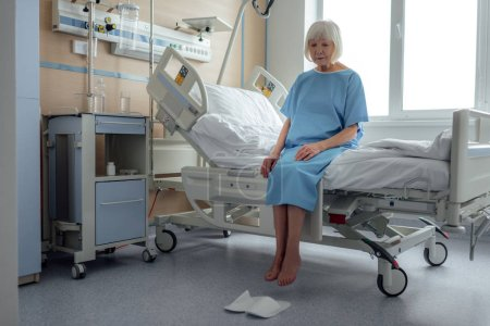 upset lonely senior woman sitting on bed in hospital ward