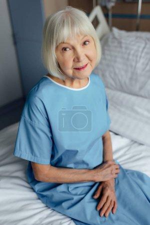 Photo pour Femme senior souriante avec les mains jointes, assis sur le lit et regarder la caméra à l'hôpital - image libre de droit