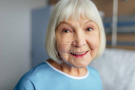 Photo pour Portrait d'une femme senior heureuse avec des cheveux gris, en regardant la caméra à l'hôpital - image libre de droit