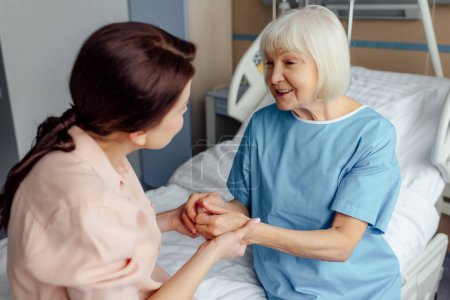 happy senior woman and daughter sitting on bed and holding hands in hospital
