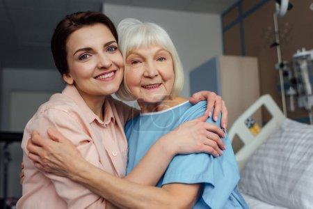 Photo pour Souriant senior femme et sa fille assise sur le lit, regardant la caméra et faire place à l'hôpital - image libre de droit