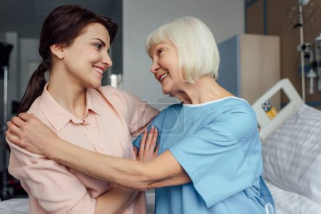 happy senior woman and daughter sitting on bed and embracing in hospital