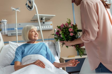daughter presenting flowers to happy senior woman in hospital