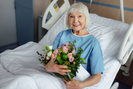 Photo for Happy recovering senior woman lying in bed with flowers and looking at camera in hospital - Royalty Free Image