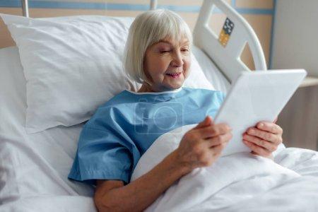 Photo pour Femme âgée souriante couchée au lit et utilisant une tablette numérique à l'hôpital - image libre de droit