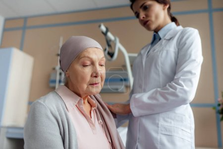 female doctor consoling sad senior woman in kerchief with cancer in hospital