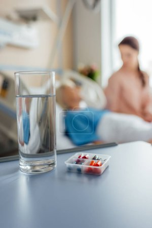 selective focus of water glass and medicine with patient and visitor on background