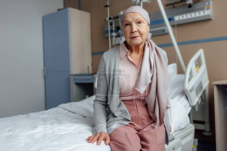 sad senior woman with cancer sitting on bed in hospital and looking at camera