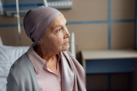 sad senior woman with cancer sitting on bed in hospital