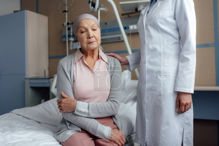 female doctor consoling upset senior woman with cancer and arms crossed in hospital