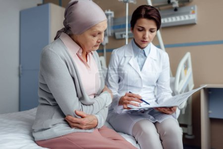 worried female doctor holding diagnosis and consulting upset senior woman with cancer in hospital