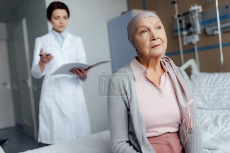 senior woman in kerchief with cancer sitting on hospital bed with female doctor holding diagnosis on background