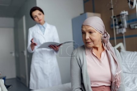 Photo for Upset senior woman in kerchief with cancer sitting on hospital bed with female doctor holding diagnosis on background - Royalty Free Image