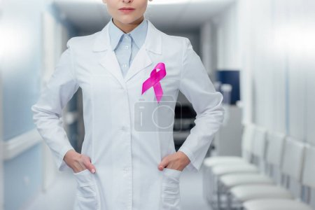 cropped view of female doctor with pink ribbon and hands akimbo in hospital, breast cancer awareness concept