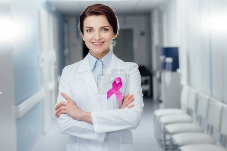 smiling female doctor with pink ribbon and arms crossed in hospital, breast cancer awareness concept