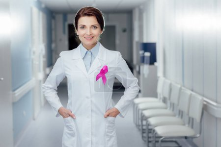 smiling female doctor with pink ribbon and hands akimbo in hospital, breast cancer awareness concept