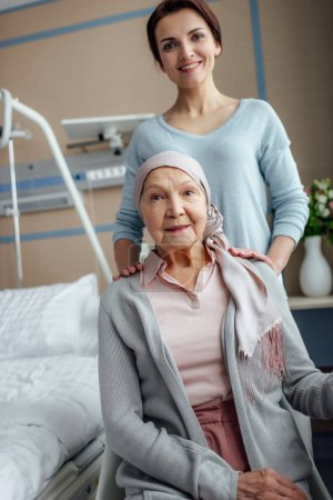 smiling senior woman in kerchief with daughter looking at camera in hospital
