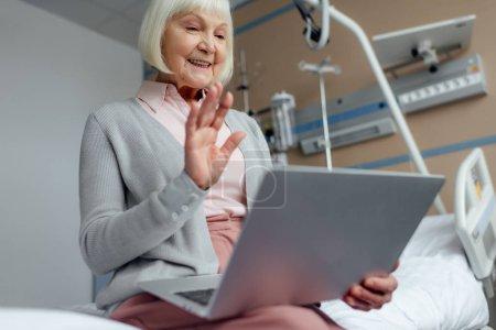 Foto de Mujer senior feliz sentado en la cama, usando laptop y saludando con la mano teniendo video llamada en el hospital - Imagen libre de derechos