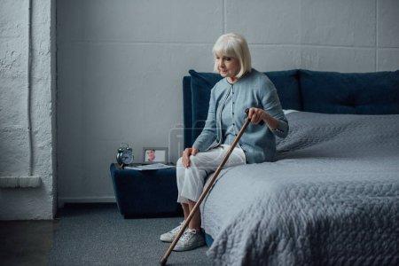 Photo pour Femme senior songeuse solitaire assis sur le lit avec le bâton de marche à la maison - image libre de droit