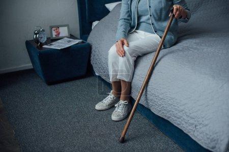 Photo pour Recadrée vue des haute femme assis et tenant le bâton de marche dans la chambre - image libre de droit