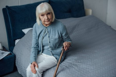 sad senior woman looking at camera and sitting on bed with walking stick at home