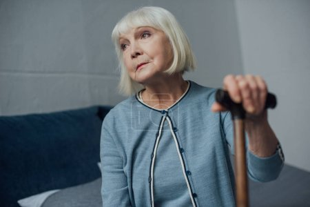lonely senior woman sitting on bed with walking stick at home