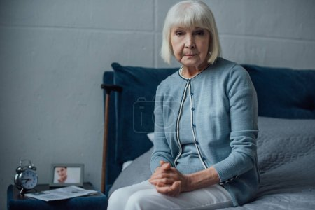 Photo for Senior woman looking at camera and sitting on bed with folded hands at home - Royalty Free Image