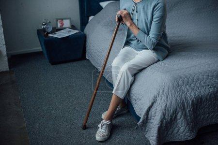 Photo pour Vue partielle de haute femme assise sur le lit avec le bâton de marche à la maison - image libre de droit