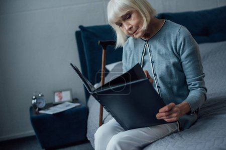 sad senior woman sitting on bed and looking at photo album at home