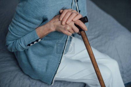Photo pour Recadrée vue des haute femme assise sur le lit avec le bâton de marche à la maison - image libre de droit