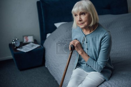 Photo for Thoughtful senior woman sitting on bed with walking stick at home - Royalty Free Image