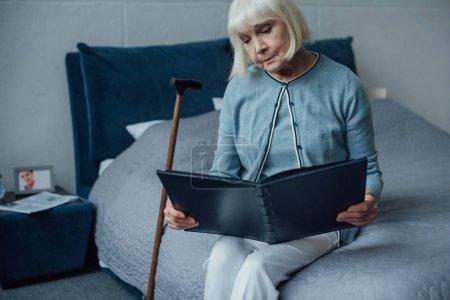 Photo pour Femme senior solitaire assis sur le lit et en regardant d'album photo à la maison - image libre de droit