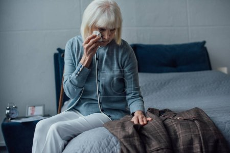 selective focus of crying senior woman sitting on bed, wiping tears and looking at jacket at home