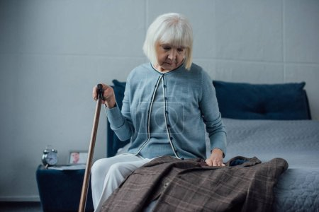 sad senior woman sitting on bed, holding walking stick and looking at jacket at home
