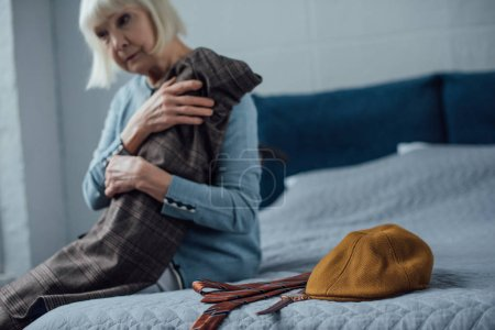 sad senior woman sitting on bed and holding jacket at home