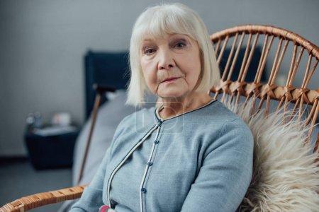 Foto de Grave mujer mayor sentada en la mecedora de mimbre en casa y mirando a cámara - Imagen libre de derechos