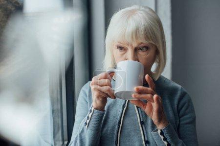 Photo pour Haute femme avec des cheveux gris, boire du café à la maison - image libre de droit