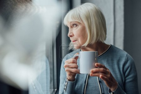 Photo for Thoughtful senior woman holding cup of coffee at home and looking away - Royalty Free Image