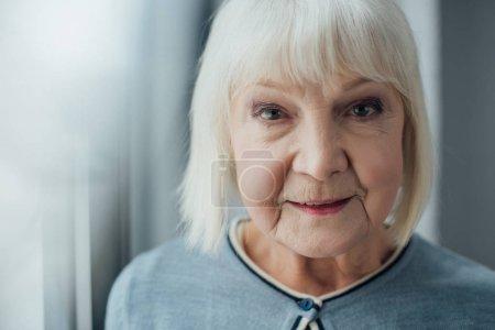 Photo pour Portrait d'une femme senior souriante aux cheveux gris, regardant la caméra à la maison - image libre de droit