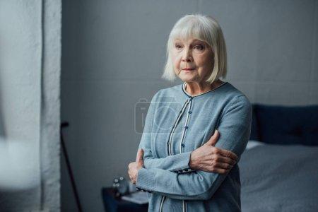 mujer mayor reflexiva en suéter casual con los brazos cruzados en casa