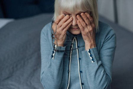 upset senior woman with glasses and grey hair wiping tears and crying at home
