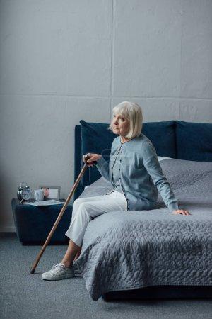 Photo pour Haute femme à la recherche de loin et assis sur le lit avec le bâton de marche à la maison - image libre de droit